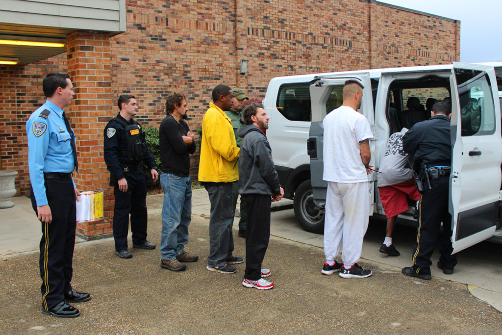 Deputies escort individuals arrested as part of Thursday's roundup.