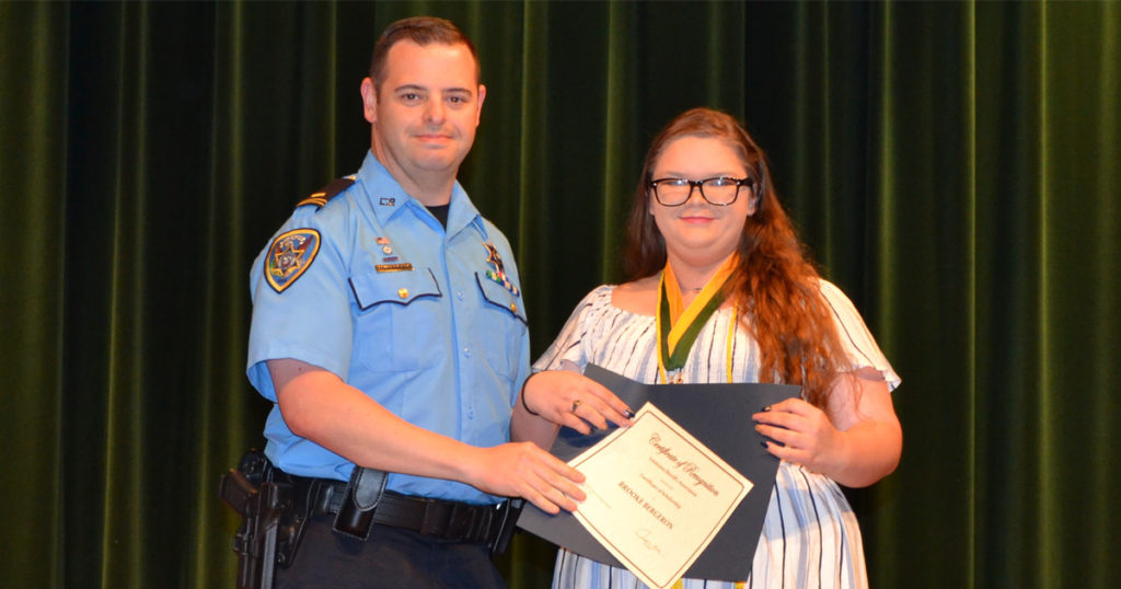 Lt. Brennan Matherne presents a certificate for the LSA Scholarship to Brooke Bergeron.