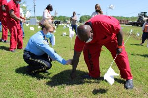 Captain Karla Beck assists Inmate Kendrick Posey in planting a white flag.