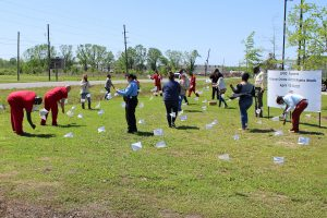 Participants in the White Flag Exposition plant flags on the front lawn of the Lafourche Parish Correctional Complex.